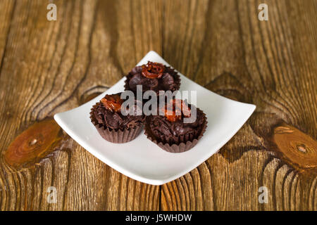 Set of chocolate candies with a fondant and dried tomato. Close up on the wooden background. - Stock Photo
