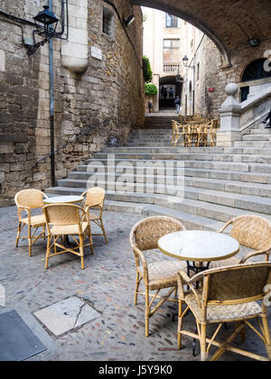 Tables and cane chairs set up for al fresco dining at the base of  the stairs of Pujada de Sant Domènec, Girona, - Stock Photo