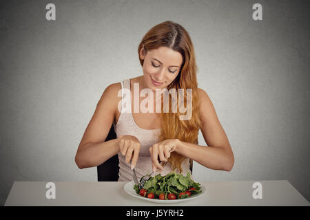 portrait attractive smiling young woman eating green salad isolated on grey wall background studio shot. healthy - Stock Photo
