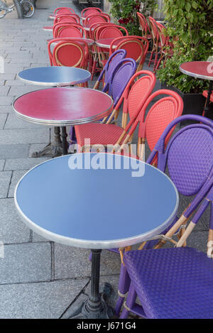 Colored tables and chairs on a sidewalk cafe in Paris -France - Stock Photo