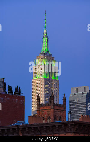The Empire State Building at twilight illuminated in green light. New York City (view from the Highline in Chelsea) - Stock Photo