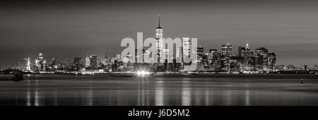 Panoramic view of Lower Manhattan Financial District skyscrapers in Black & White at dawn from New York City Harbor - Stock Photo