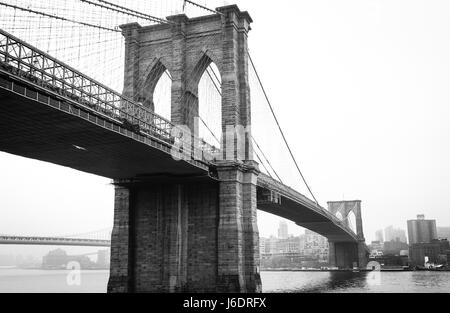 Black and White picture of the Brooklyn Bridge with Manhattan in the Background - Stock Photo