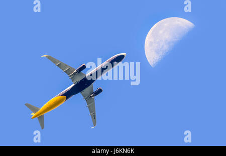 Fly me to the moon. Passenger jet aeroplane flying high against blue sky with the moon in the distance. Air travel. - Stock Photo