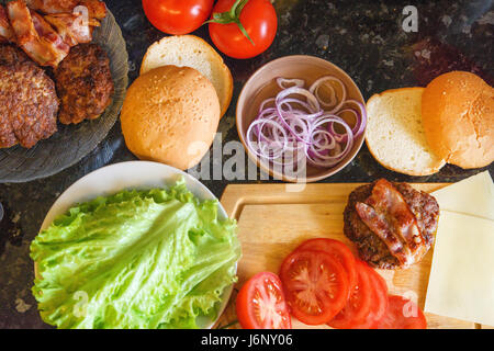 Homemade burger ingredients: burger cutlet, lettuce, tomato, buns, bacon, cheese and onion - Stock Photo
