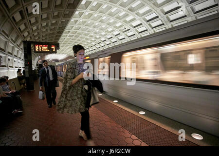 passengers and moving train at smithsonian metro underground train system Washington DC USA deliberate motion blur - Stock Photo