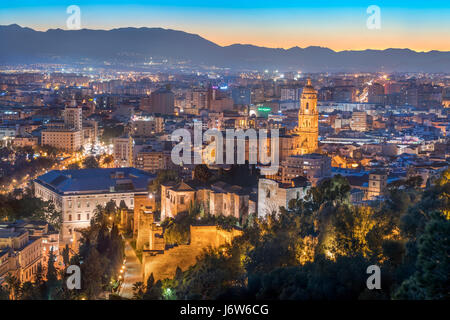 Malaga Cathedral with Old Town scenic view from Gibralfaro with the Alcazaba castle at sunset twilight dusk evening - Stock Photo