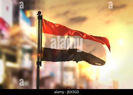 Yemen Flag Against City Blurred Background At Sunrise Backlight - Stock Photo
