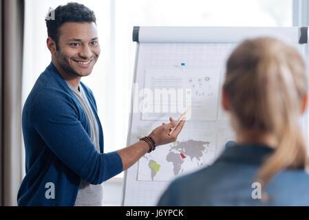 Happy joyful nice man standing in front of the flip chart - Stock Photo