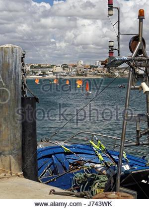 Optimist sailing boats with orange sails,against cloudy sky, Cascais, Portugal - Stock Photo