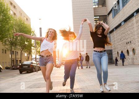 Three happy young women running hand in hand on sidewalk - Stock Photo