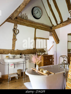 Vaulted bathroom with ancient beams and roll-top French bath. The basin is from Duravit - Stock Photo