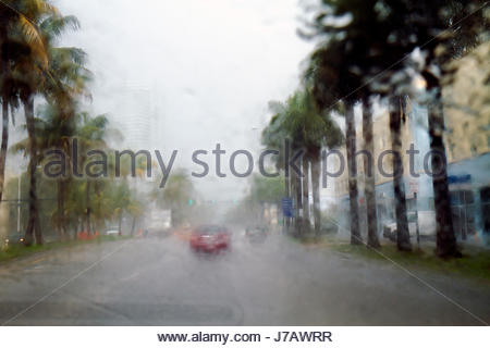 Miami Beach Florida 5th Fifth Street heavy rain storm view through front windshield window car automobile limited - Stock Photo