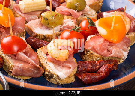 Set of canapes with ham, prawn, tomato and olives on blue plate - Stock Photo
