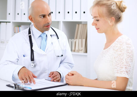 Confident bald doctor man consults his female patient - Stock Photo