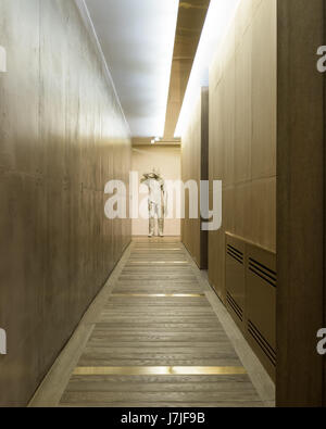 Figure in compressed glass shielding eyes by Daniel Arsham in hallway with polished concerete walls - Stock Photo
