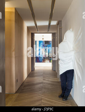 Shrouded figure sculpted from powdered glass by Daniel Arsham in hallway with painting by Oliver Masmonteil - Stock Photo