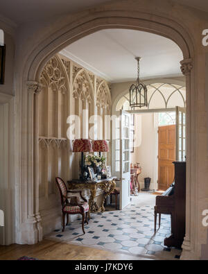Giltwood console table in entrance hall with Oka lamps and gothic details - Stock Photo