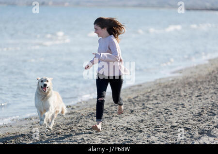 Teenage girl playing with her dog on a beach. Shot taken in Santa Pola in the province of Alicante, Spain. - Stock Photo