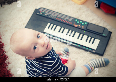 Little baby boy plays on keyboard toy. baby piano music playing child white cute little concept - Stock Photo