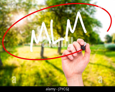 Man Hand writing  MLM (Multi-Level Marketing) with black marker on visual screen. Isolated on background. Business, - Stock Photo