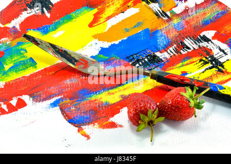 The painting knives and strawberry put on painting canvas - Stock Photo