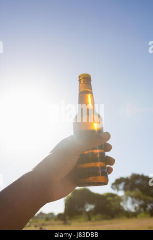Hand of man holding a beer bottle in the park on a sunny day - Stock Photo