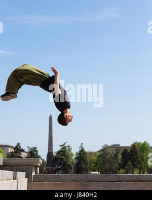 Young man doing a back flip in the background obelisk. Parkour in the urban space. Sports in the city. Sport activity. - Stock Photo