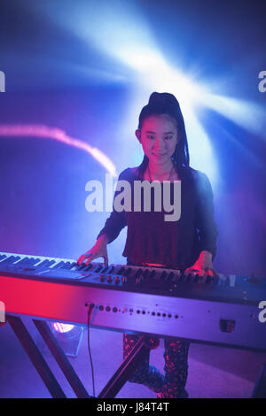 Portrait of smiling female musician playing piano in illuminated nightclub - Stock Photo