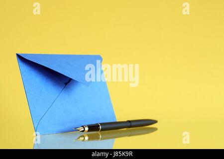 Blue envelope near fountain pen on yellow background - Stock Photo