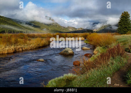 Clouds rolling in on Morraine Park in Rocky Mountain National Park with the Big Thompson flowing in the foreground - Stock Photo