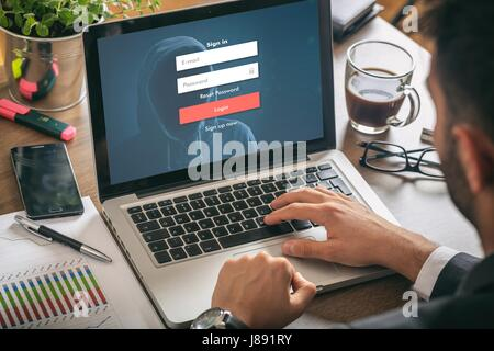 Internet security concept - Young man in his office, login on the laptop screen - Stock Photo