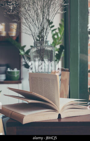 Open book left on the table - Stock Photo