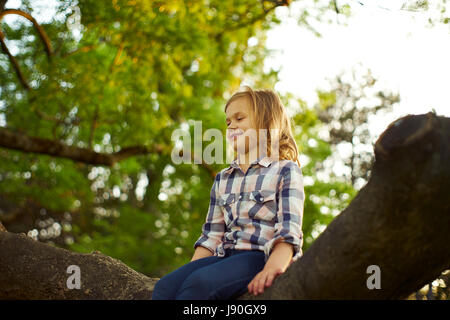 A girl sitting on a tree - Stock Photo