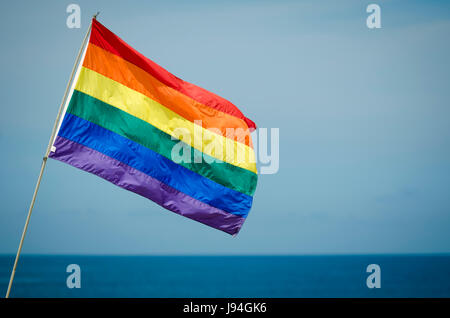 Gay pride rainbow flag flying outdoors in bright summer sun above the ocean horizon in Fire Island, New York - Stock Photo