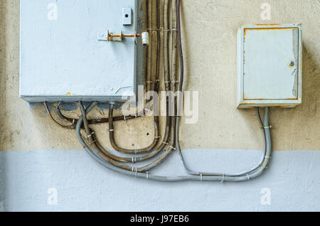 Electrical switchboard on the wall. Wiring to the electrical panel on the wall. Detail of the cityscape. Grey wall - Stock Photo