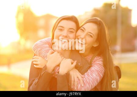 Front view portrait of two happy friends laughing and posing looking at you in the street at sunset with a warm - Stock Photo