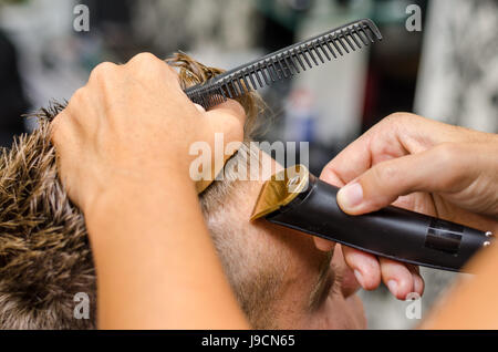 Barber cutting and modeling hair by electric trimmer - Stock Photo