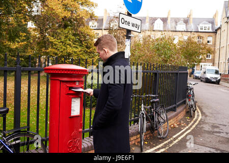 OXFORD/ UK- OCTOBER 26 2016: Man Posting Letter In Royal Mail Postboxperson,person,people,caucasian,20s,twenties,england,horizontal,autumn,fall,copy - Stock Photo