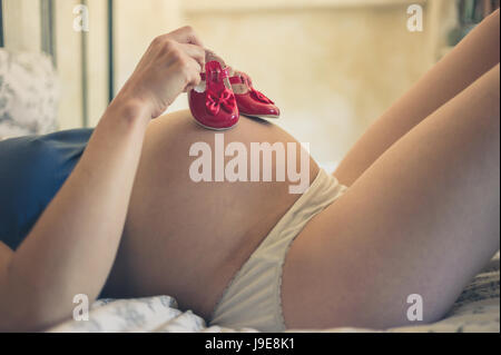 A young pregnant woman is lying in bed at home with baby shoes on her belly - Stock Photo