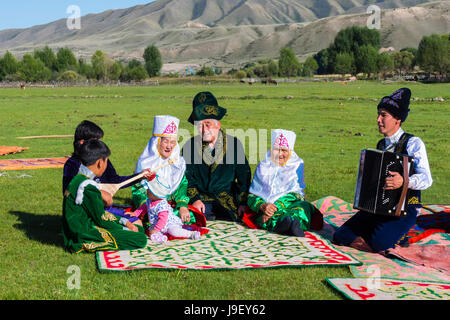 Kazakh family in traditional clothes listening to the music of an accordion player, For editorial Use only, Sati - Stock Photo