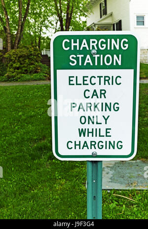 Charging station sign indicating parking for electric cars only and only while charging. - Stock Photo