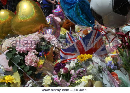 A Union Jack flag stands among balloons and flowers in St Ann's Square Manchester after the Manchester bombing - Stock Photo