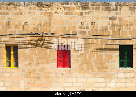 Three colourful windows painted yellow, red and green  in an old stone building in Marsaxlokk Malta - Stock Photo