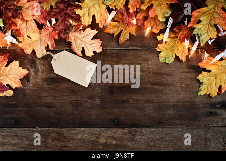 Rustic fall background of autumn leaves and decorative lights with empty tag for copy space over a rustic background - Stock Photo