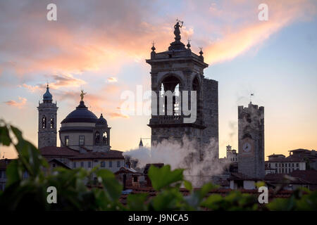 View of the upper town of Bergamo (Italy) at sunset. It's possibile to see the civic tower, the - Stock Photo