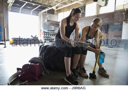 Personal trainer with digital tablet talking to female client with sledgehammer at crossfit training gym - Stock Photo