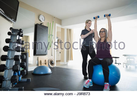 Female physiotherapist working with client exercising on fitness ball in clinic gym - Stock Photo