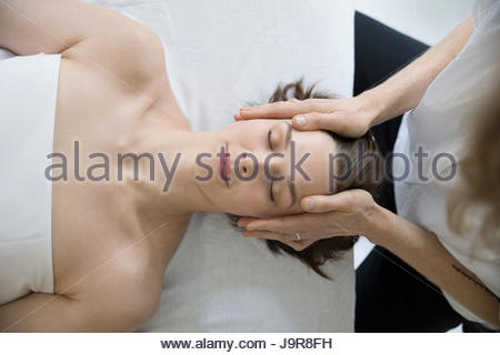 Overhead view serene woman receiving face and scalp massage - Stock Photo