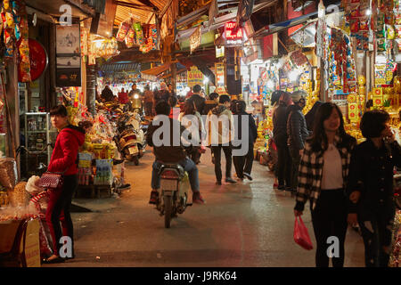 Motorcycle and shoppers in night market, Old Quarter, Hanoi, Vietnam - Stock Photo